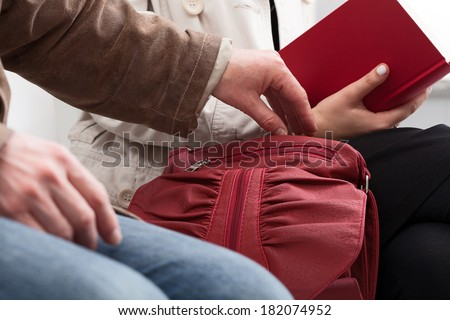 Man trying to steal something lady sitting in waiting room - stock photo
