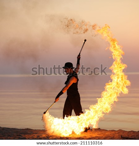 Man twirling fire batons on the beach - stock photo