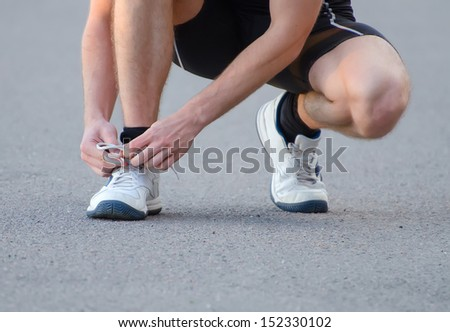 Man tying his sport shoes - stock photo