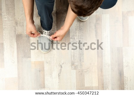 Man tying shoes laces on wooden parquet background - stock photo