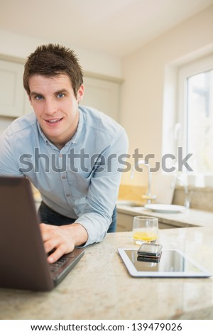 Man typing at the notebook with smartphone and tablet in kitchen - stock photo