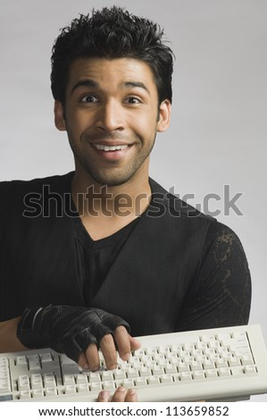 Man typing on a computer keyboard and smiling - stock photo