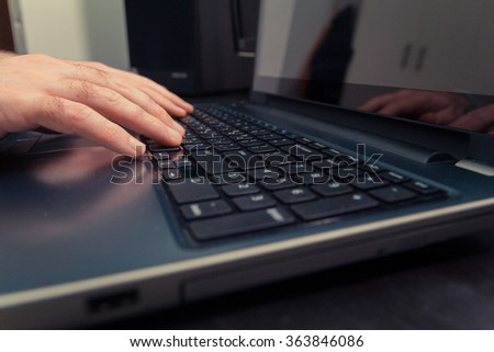 Man typing on a keyboard with letters in Hebrew and English - Laptop keyboard