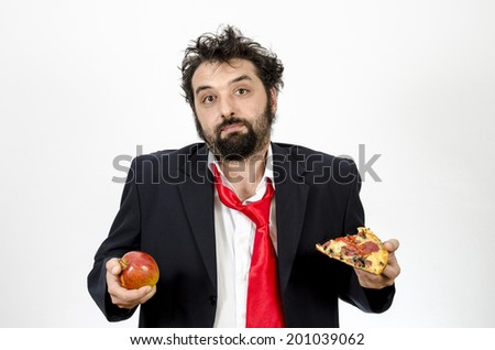 Man Undecided Between An Apple Or A Slice Of Pizza - Healthy Food Versus Unhealthy Food - Isolated On White /  Food Choice