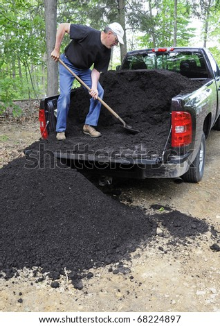Man unloading compost from pickup truck - stock photo