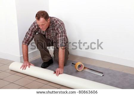 Man unrolling carpet - stock photo