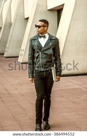 Man Urban Autumn/Spring Casual Fashion. Wearing black leather jacket, white undershirt, black bow tie, jeans, sunglasses, carrying laptop computer, African American guy walking on street in New York. - stock photo