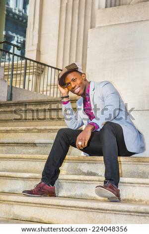 Man Urban Fashion. Wearing a Newsboy cap, dressing in light gray blazer, patterned pink, black under shirt, black pants, brown leather shoes, a young guy is sitting on stairs, smiling, relaxing.