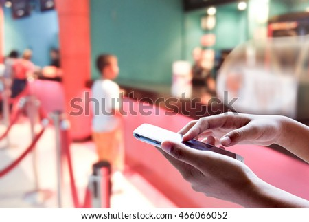 Man use mobile phone, blur image of kid buying movie ticket as background.
