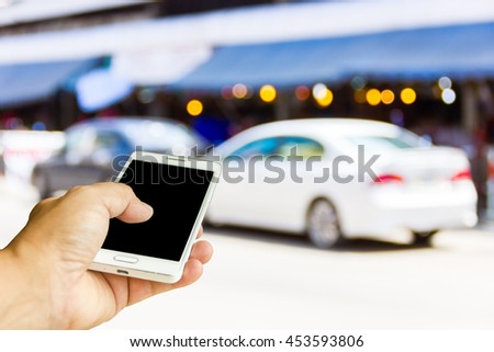 Man use mobile phone, blur image of the car was parked on the street as background.