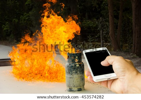 Man use mobile phone, gas tank fired as background. - stock photo
