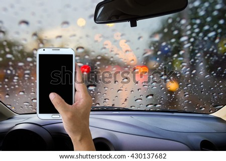 Man use mobile phone in the car, blur image of heavy rain on the road at night as background. - stock photo
