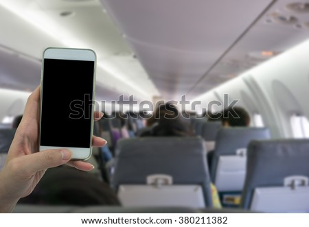 Man use your phone in airplane blurred background - mockup template - stock photo