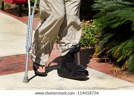 Man uses crutches along with a foot and ankle brace to help him walk after an accidental injury. - stock photo
