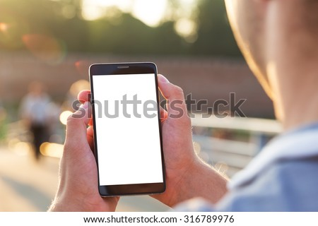 Man uses his Mobile Phone outdoor, close up - stock photo