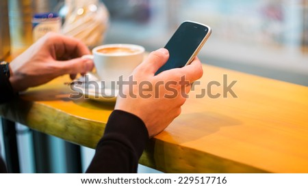 Man using a cell phone on cafe terrace and drink coffee - stock photo
