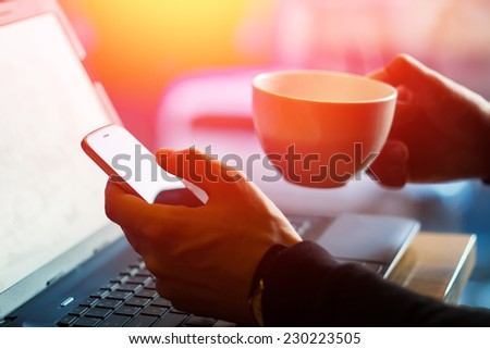 Man using a cell phone on cafe terrace and drinking coffee. Man drinks coffee. Man using cellphone. Man with laptop, cellphone and coffee. Mans hands with cell phone, laptop, coffee. Mans hands.