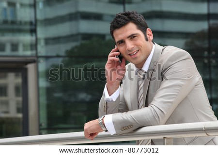 Man using a cellphone outside an office building - stock photo