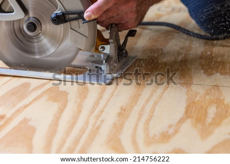 Man using a circular saw to cut plywood - stock photo