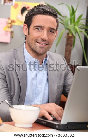 Man using a laptop in his kitchen - stock photo