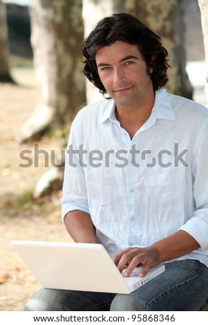 Man using a laptop outdoors - stock photo