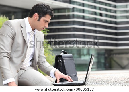 Man using a laptop outside - stock photo