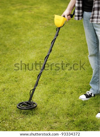 Man using a metal detector on lawn.