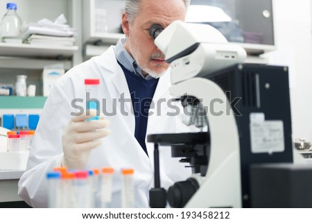Man using a microscope in a chemical laboratory - stock photo