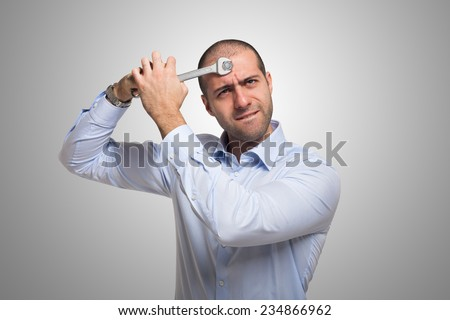 Man using a 19mm wrench to fix his brain - stock photo