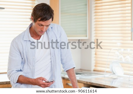 Man using a mobile phone in his kitchen - stock photo