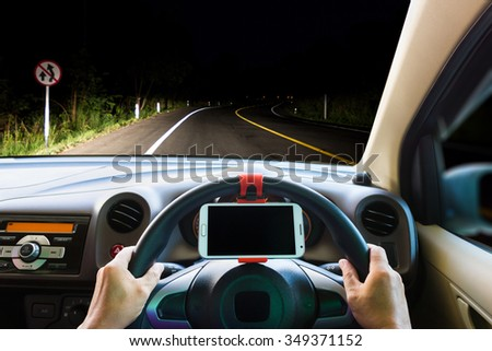 Man using a mobile phone while driving in the dark .