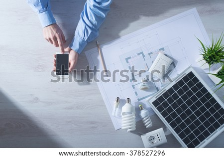 Man using a mobile touch screen smart phone next to a solar panel, a set of CFL lamps and a house project, energy saving concept - stock photo