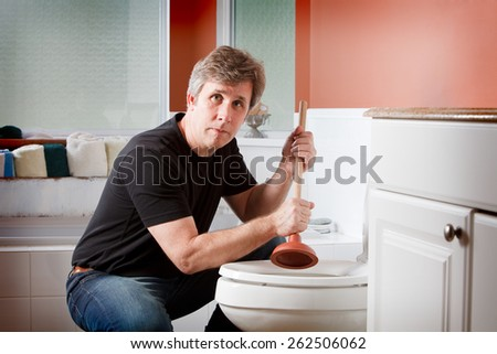 Man using a plunger to clear a plugged toilet - stock photo
