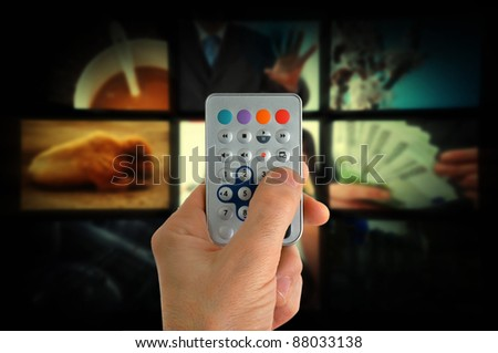 Man using a remote control and changing TV channels. - stock photo