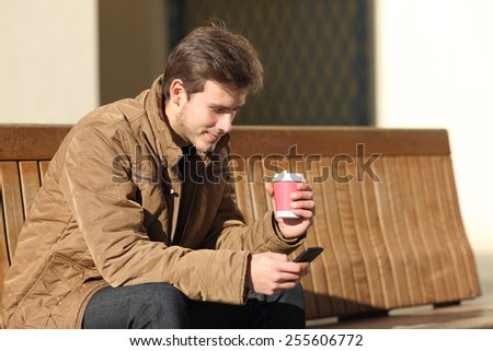 Man using a smart phone and holding a coffee cup sitting in a bench in the street - stock photo