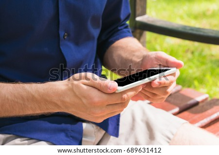 man, using a smart phone in the hands, sitting in the park outdoors