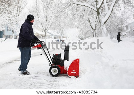 Man using a snow blower to clear out his driveway - stock photo