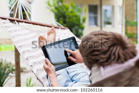 Man using a tablet computer while relaxing in a hammock - stock photo