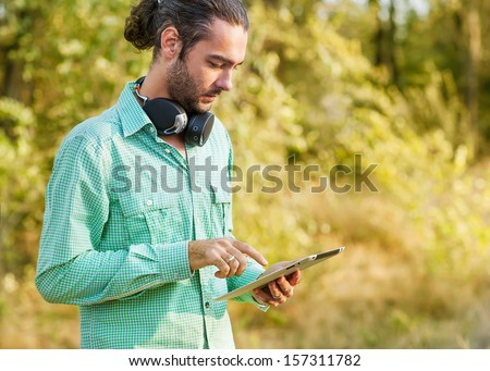 Man using a tablet computer while relaxing  outdoor - stock photo
