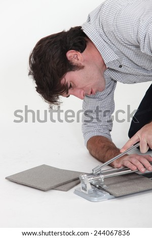 Man using a tile cutter - stock photo