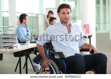 Man using a wheelchair in an office environment - stock photo