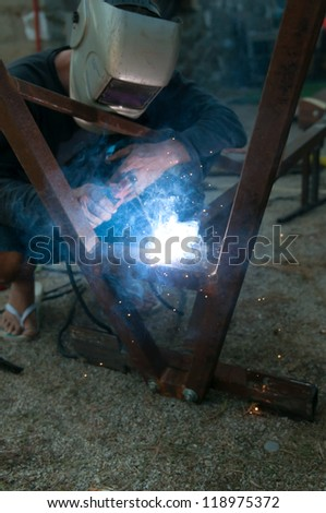 Man using an arc welder - stock photo