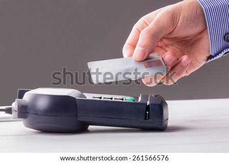 Man using card to express pay against grey background - stock photo