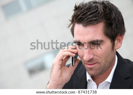 Man using cellphone in town - stock photo