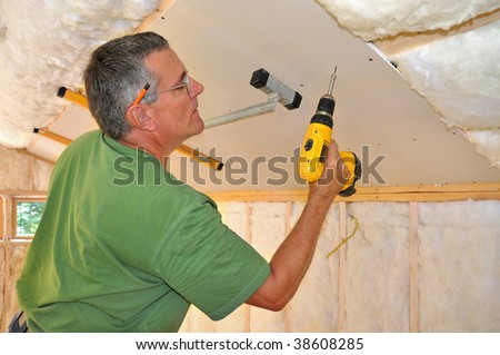 Man using cordless drill to attach drywall panel to ceiling - stock photo
