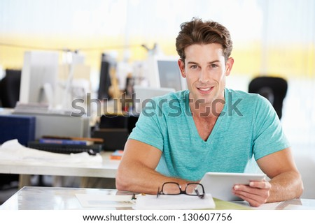 Man Using Digital Tablet In Busy Creative Office - stock photo