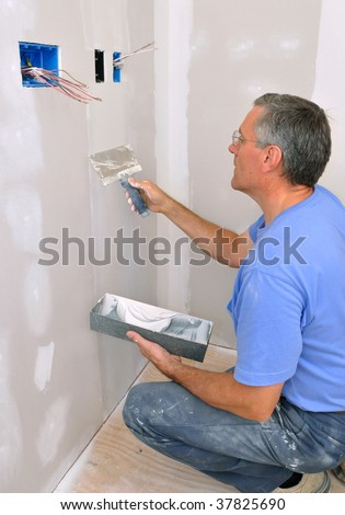Man using drywall knife to finish seam between drywall sheets - stock photo