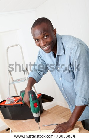 Man using electric drill at home - stock photo