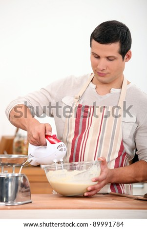 Man using electric whisk - stock photo