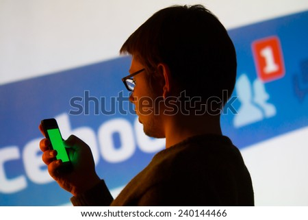Man using Facebook application on his smartphone, background is a image from the projector - photography from social media meeting in city of Lodz, Poland 07.11. 2014 - stock photo